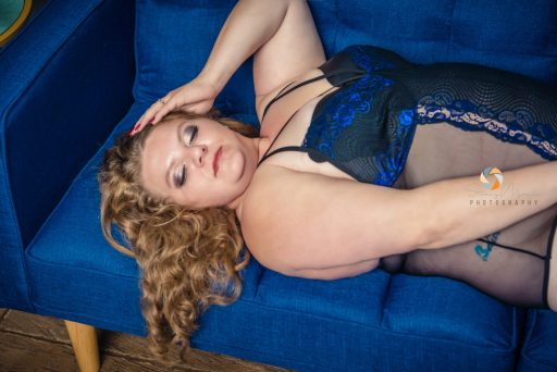 Sexy boudoir photograph on a blue couch with blue lingerie.