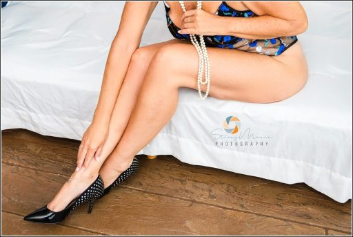 A woman sitting on a bed holding a string of pearls reaches down to touch her legs.