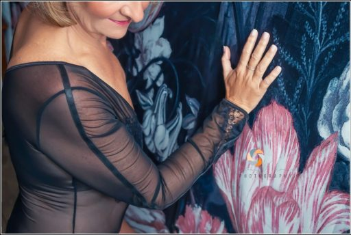 A woman in a long sleeve black lace lingerie leans against a floral wall.
