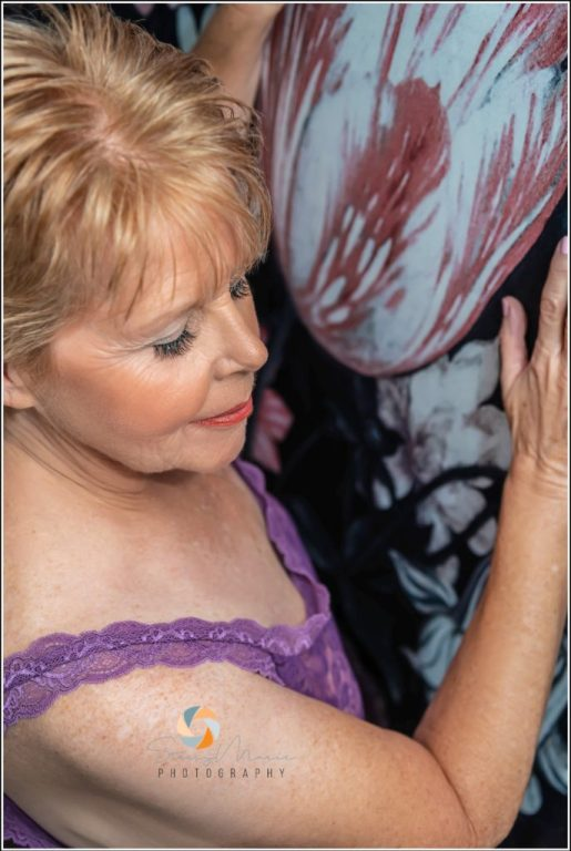 An older woman stands next to a floral wall in purple lingerie while posing for a boudoir session as she steps out of the box of her comfort zone.