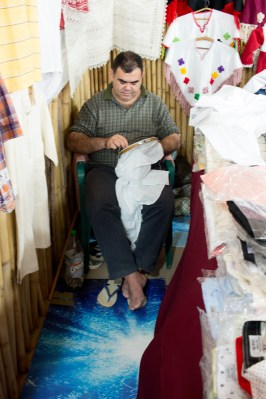 A man hand embroidering dress shirts