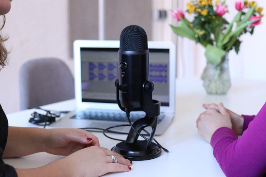 Centre of image is sturdy looking microphone used for podcasting. In the background is an open lap top and on the screen you can see the sound waves of what is being recorded. In the foreground you can see the arms of two people who are in conversation.