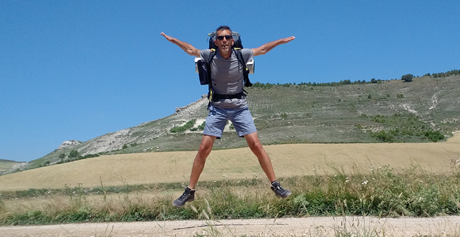 Steve Stachini CV image showing Steve doing a star jump on the Camino de Santiago