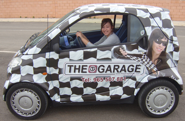 Steve Stachini BIO pic - A smart car vehicle wrapped in a checked flag background graphic design for The Garage, Alicante, Spain.
