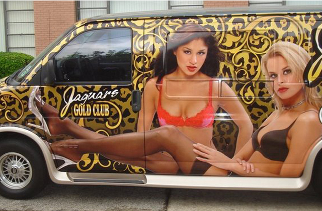 Steve Stachini BIO pic - A medium sized van, vehicle wrapped in with the graphic design of a generic gold swirl background and two half naked female models on the sides, for The Jaguar Club.