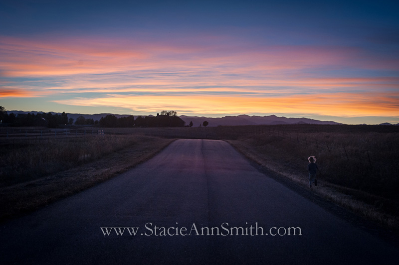 Photograph of a sunset with a kid running alongside the road near Denver