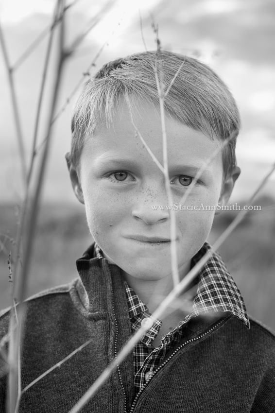 b&w photograph of boy holding a stick