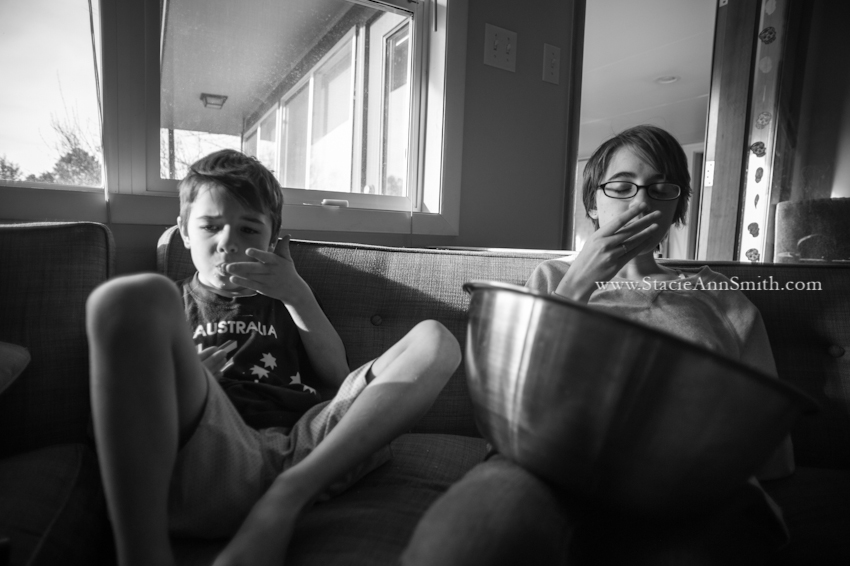 A b&w photograph of two kids eating from a huge bowl of popcorn at their home in Denver