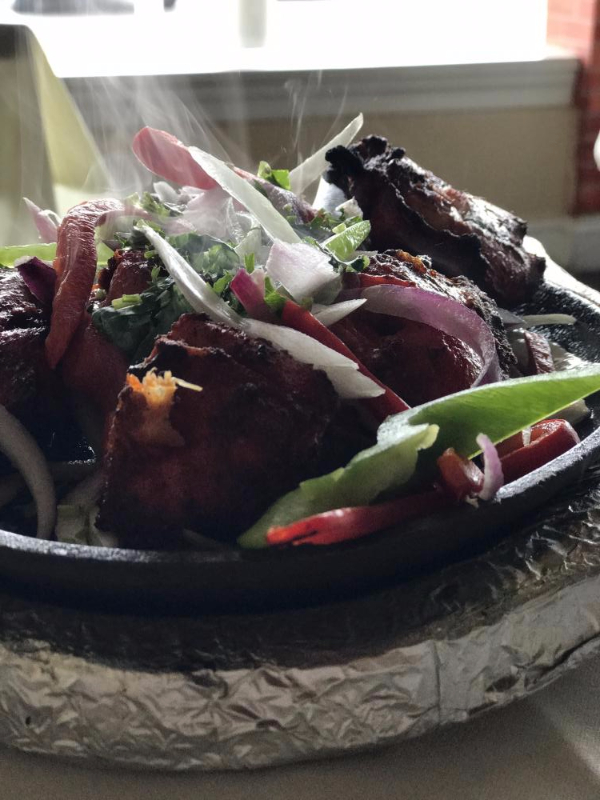 steaming tandoori chicken and vegetables close-up