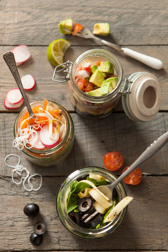 Three different lunch jar ideas with different meals open and being eaten with mess all over the grey rustic wooden surface