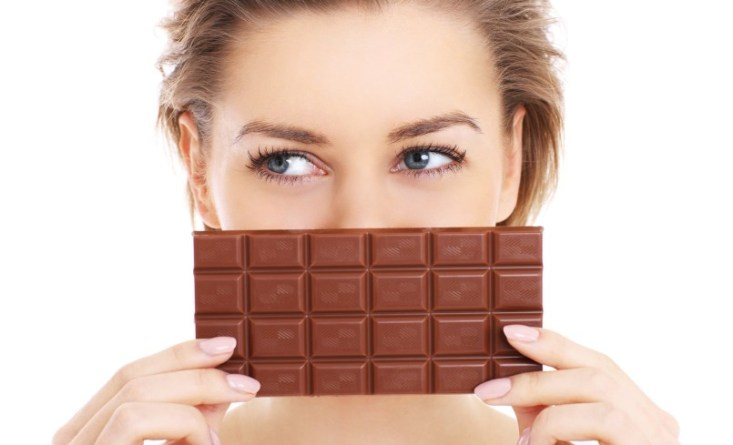 A picture of a pretty woman holding chocolate over white backgro