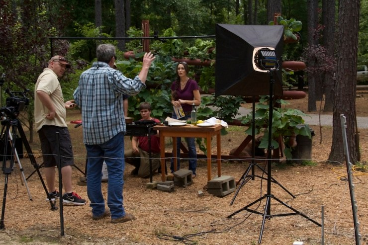 Stacy Lyn Harris filming in front of hydroponics gardening system.