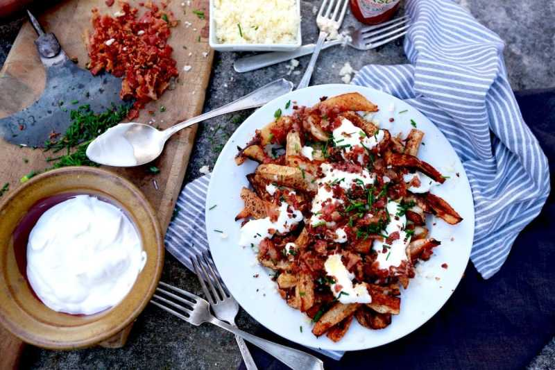 Turnip Root - Loaded Baked Turnip Fries on cement table with bacon, chives, sour cream on a white plate with a striped napkin under it