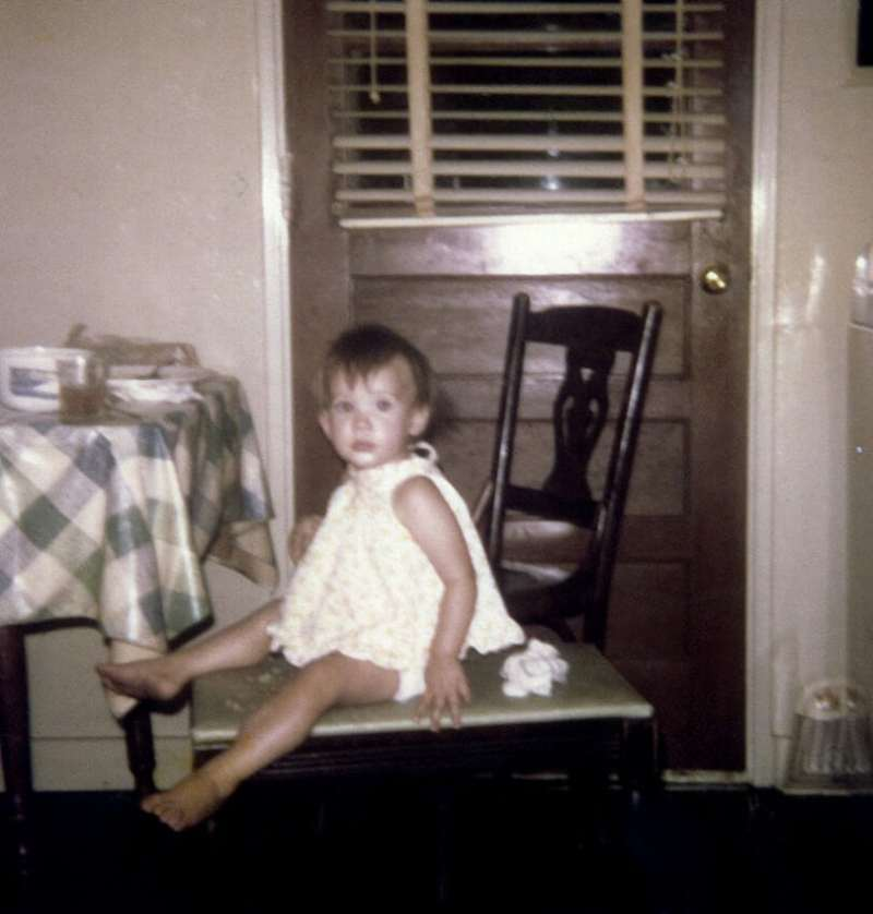 Stacy as a child sitting at her grandmother's table