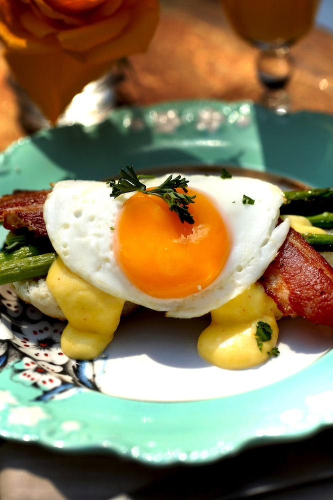 Southern-style eggs benedict over biscuits, asparagus and hollandaise sauce