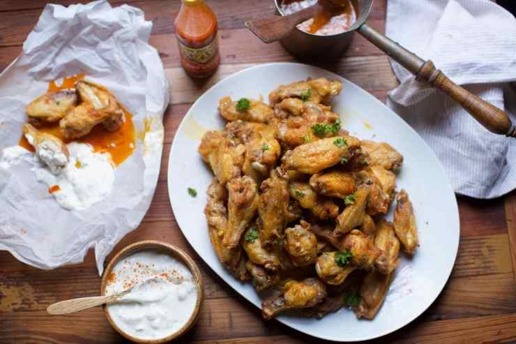 Full spread of spicy chicken wings and blue cheese dressing
