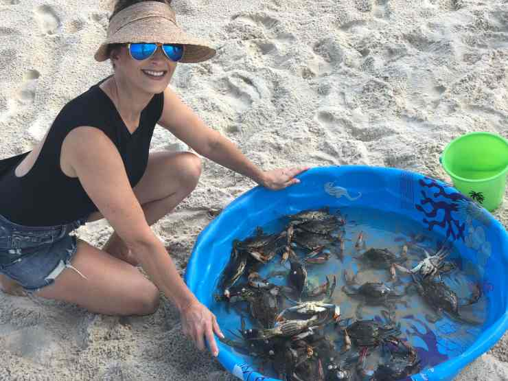 stacy lyn harris next to a kiddie pool filled with freshly caught crab