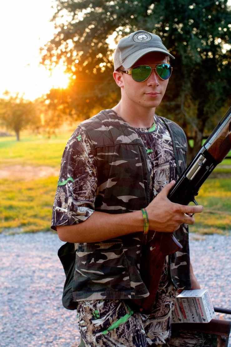 Stacy Lyn's son decked out in full camo and hunting gear holding a shotgun in preparation for the dove hunt