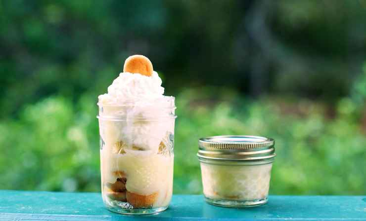 Banana pudding in mason jars, topped with vanilla wafers and whipped cream