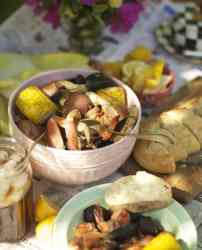 Clam bake scene featuring seafood and corn on a newspapered table.