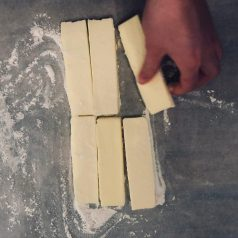 Sprinkle a little flour over the butter and parchment paper and roll the butter into a flat sheet with the rolling pin (recipe for how to make danish pastries by Stacy Lyn Harris)