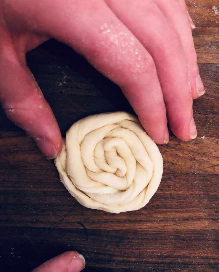 Roll one end of the spiral dough continuously to reach the other end (recipe for how to make danish pastries by Stacy Lyn Harris)