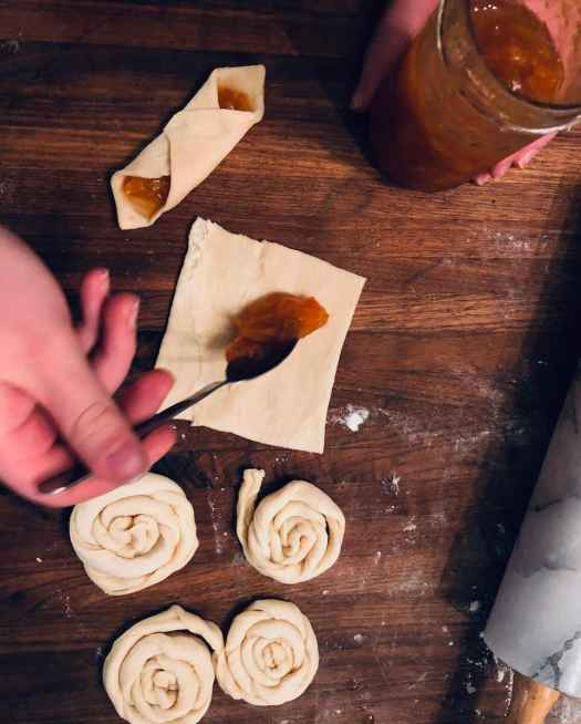 Place cream, pastry cream, or jelly diagonally into square pieces of dough. Fold the sides and seal the pastry together with an egg wash (recipe for how to make danish pastries by Stacy Lyn Harris)