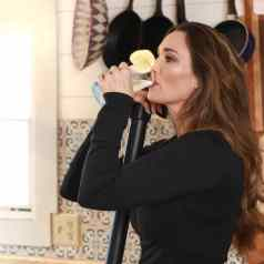 Stacy Lyn Harris drinking a cup of ice water with lemon, illustrating her point about health benefits of hydration