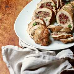 Turkey Breast Stuffed with Sausage and Cranberries on a white plate on a wooden table with a linen napkin