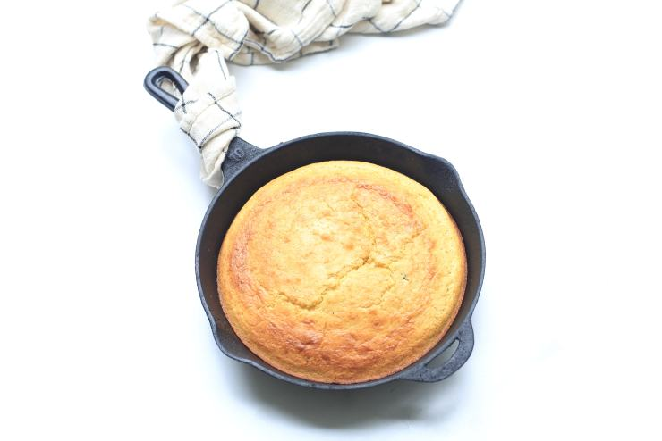 Cornbread in Black Skillet with Towel on White Background