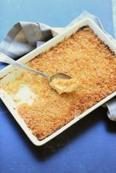 Squash casserole with ritz cracker topping in white rectangle pan over bright blue background
