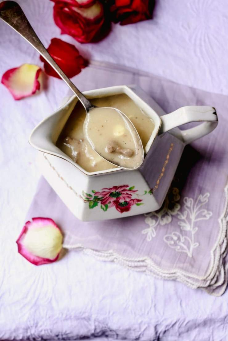Giblet Gravy in a rose stenciled serving dish with spoon of gravy laying on top and rose petals surrounding it on lavender tablecloth