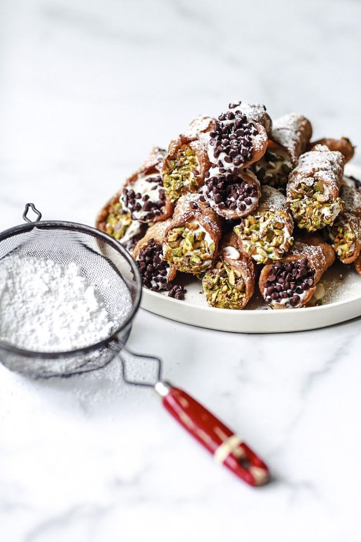Cannoli on a round plate stacked up with chocolate and pistachios on white marble with powdered sugar sprinkle