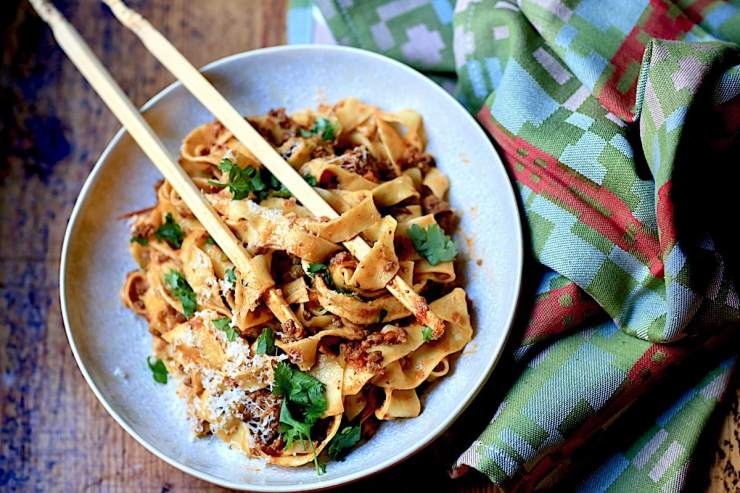 Bolognese in White bowl with Chopsticks on wooden surface with Italian napkin