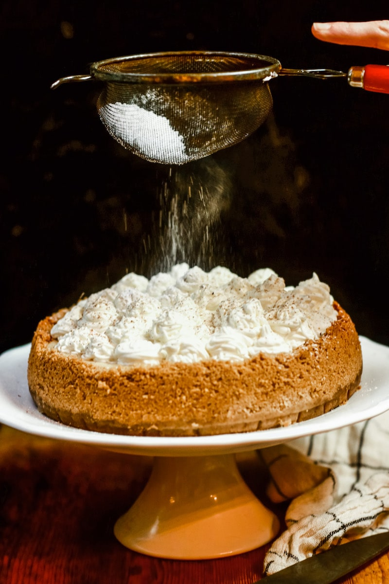 Shown with whipped cream rosettes on a white cake stand and powdered sugar being sprinkled on top
