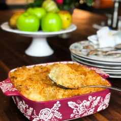 Pineapple Casserole with Buttery Tollhouse Crackers in Red Casserole Dish with White Flowers and cake stand with apples in background