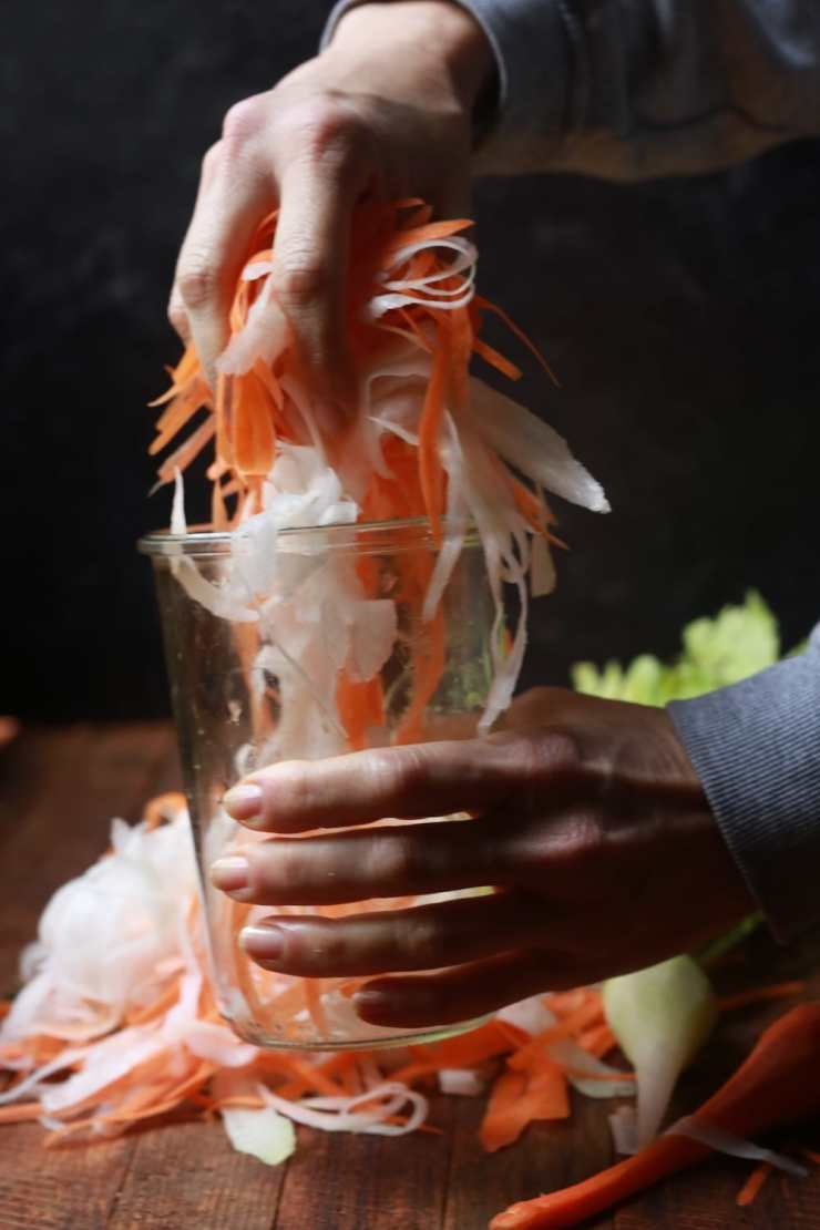 Stacy Lyn's hands putting daikon radishes and carrots in a. pickling jar