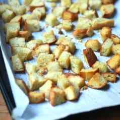Crispy sourdough croutons baked on parchment lined baking pan