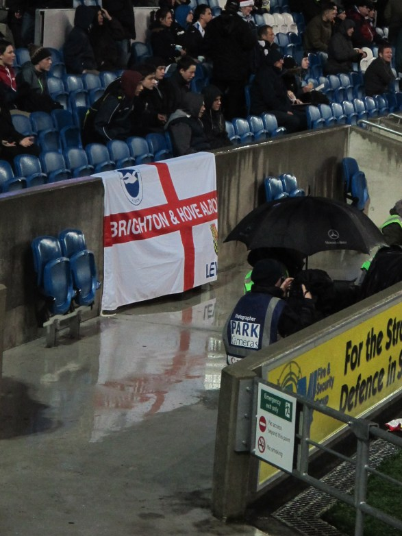 Wet reflections. It always strikes me how few flags there are at British football matches. This was one of the few. (Photo: Stadiafile)