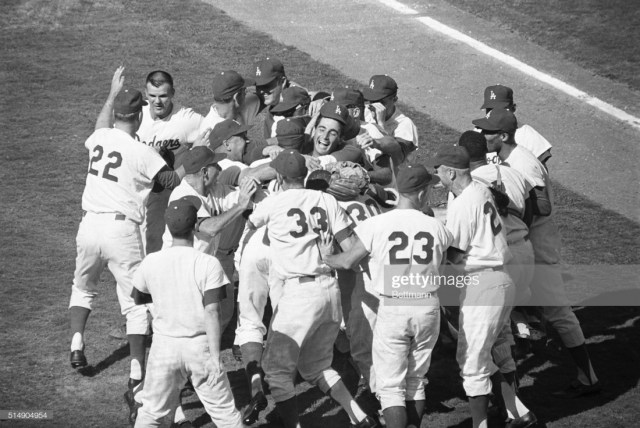 From Getty Images (Original Caption) 10/6/1963-Los Angeles, CA: Los Angeles Dodger pitcher Sandy Koufax is mobbed by his teammates, after winning the fourth straight World Series game against the New York Yankees.