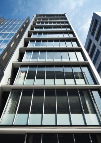 庇とフィンのあるガラスカーテンウォールによるビル外観見上げ