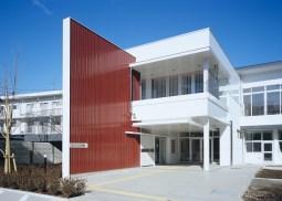 シンボリックな赤い壁が児童を誘う小学校校舎