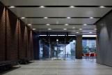 タイル外壁が内部に滑り込むオフィスビルのエントランスホールの内観写真