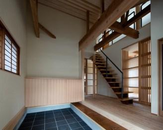 天井を取り除き木梁あわらしとした土間玄関。階段上部より光が射し込む明るい北側玄関