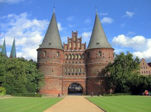 Holstentor i Lübeck med sina runda torn och konformade tak, samt mitttakgavlen. Bild: Glenn Strong.