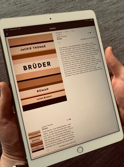 """Zwei Hände halten ein iPad auf dem Jackie Thomaes Roman """"Brüder"""" als E-Book zu sehen ist"""