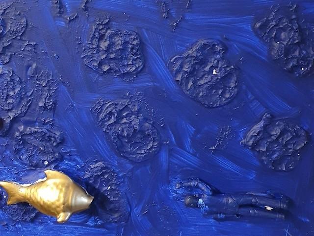Tuschebild mit dreidimensionalen Elementen: Dunkelblauer Tusche-Hintergrund mit gut sichtbaren Pinselstrichen. Viele plastische dunkelblaue Farb-Inseln erheben sich aus dem Bild. In der unteren Bildhälfte sind ein goldener Plastikfisch und eine männliche, dunkelblaue Plastikfigur auf dem Bild befestigt.