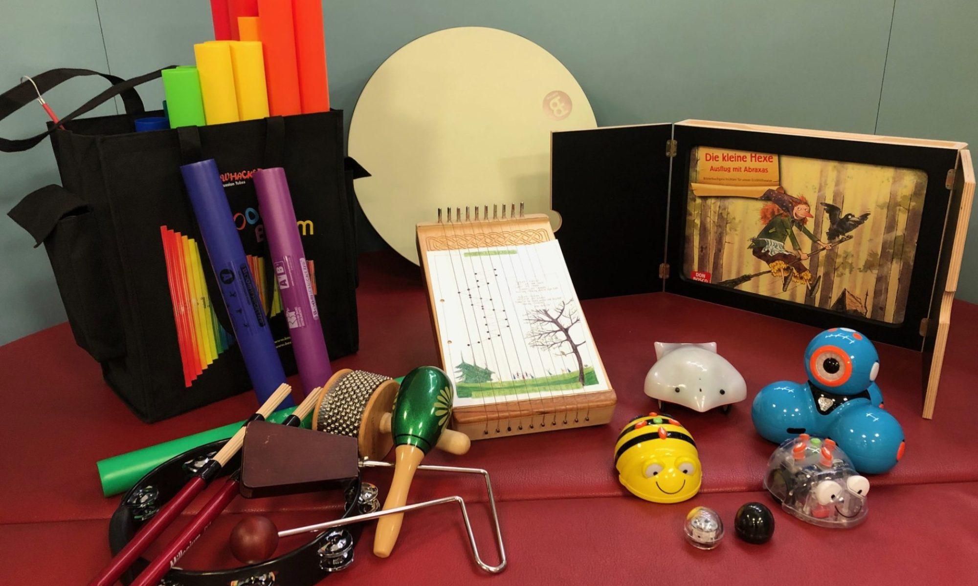 """Ein Tisch mit Instrumenten, Lernrobotern und einem Bilderbuchkino. Zu den Instrumenten gehören Rasseln, ein Tamburin, eine Tischharfe, eine Trommel und bunte Röhren verschiedener Länge. Die Lernroboter haben die Form von Käfern, Vögeln und Kugeln und bewegen sich auf Rollen. Im Rahmen des Bilderbuchkinos sieht man die Geschichte """"Die kleine Hexe""""."""