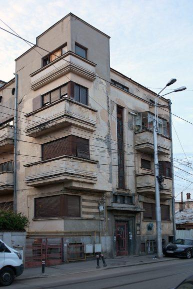 Viergeschossiges Mehrparteienhaus im Bauhaus-Stil mit Balkonen, die grau-rosa Fassade bröckelt.