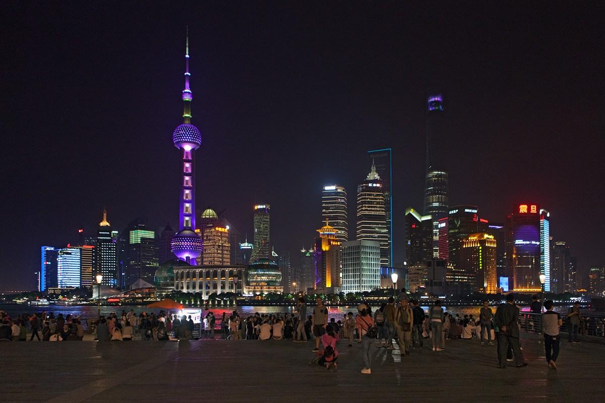 Menschen die auf die beleuchtete Skyline von Hochhäusern gucken